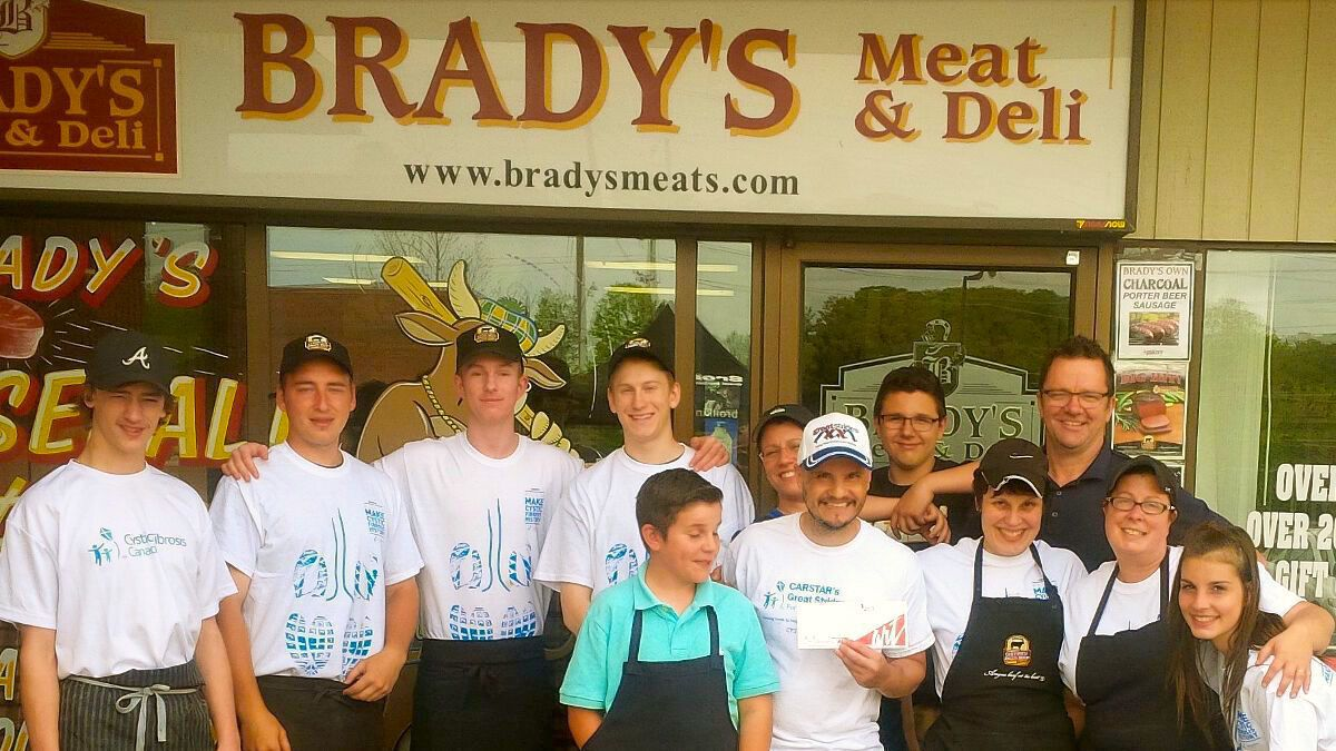 The Brady's Staff, Mike Farwell, and some volunteers in front of the store after a successful charity fundraiser.
