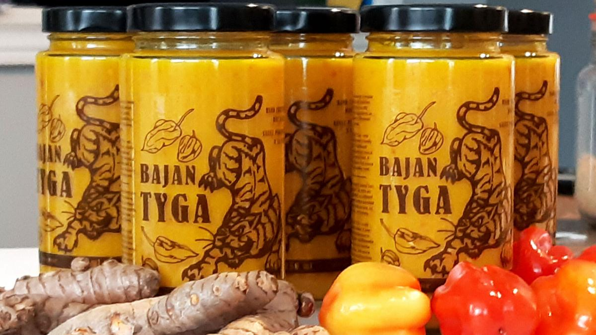 Jars of bright yellow hot sauce with a picture of a tiger and the name Bajan Tyga printed on the jar; pictured with ginger root and scotch bonnet peppers in the foreground